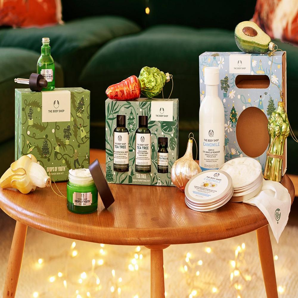 Drops of Youth and Tea Tree skincare gift sets against beige background